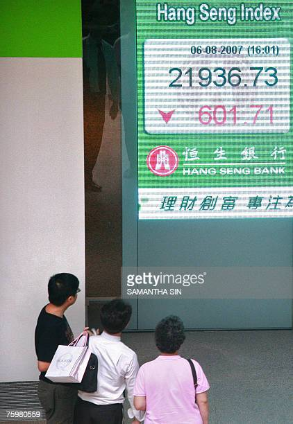 People look at the Hang Seng Index, shown on a giant digital screen at a local bank's window in Hong Kong, 06 August 2007. The Hang Seng Index closed...