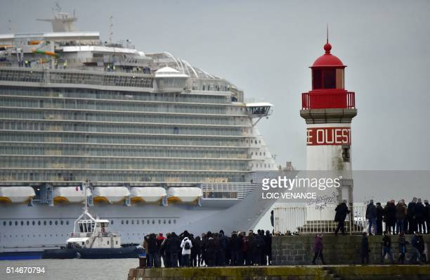 People look at the Harmony of the Seas cruise ship leaving the STX shipyard of SaintNazaire western France for a threeday test offshore on March 10...