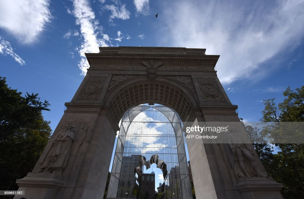 People look at the installation of Chinese Artist Ai Weiwei entitled 'Good Fences Make Good Neighbors' during a press preview under the Washington Square Arch in Washington Square Park in New York City, on October 10, 2017 ahead of October 12's public opening of his multi-venue exhibition inspired by the international migration crisis. Spread across multiple New York boroughs, the multi-site project transforms metal wire security fences into artistic symbols by installing them in varying, site-specific forms at locations across the city. /