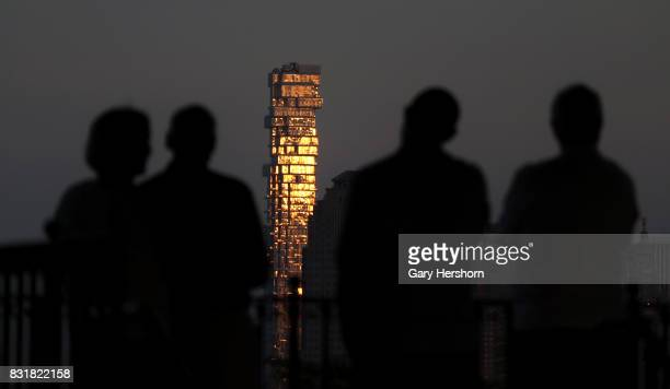 People look at the Jenga residential tower at sunset in New York City on August 13 as seen from Jersey City New Jersey
