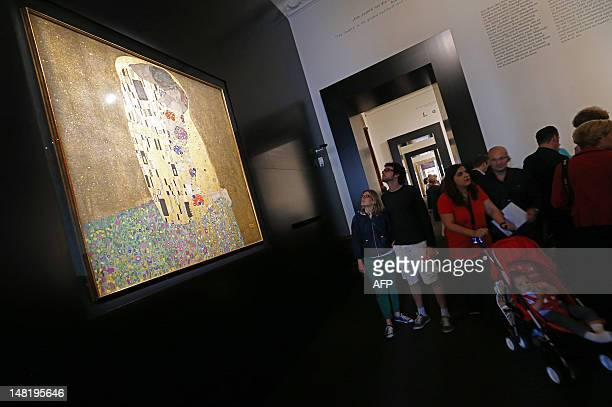 People look at 'The Kiss' painting by Austrian artist Gustav Klimt at the Belvedere Palace in Vienna on July 12 2012 On his 150th birthday Vienna's...