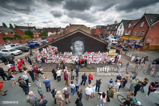 People look at the messages of support and the newly repaired mural of England footballer Marcus Rashford by the artist known as AKSE_P19, which is...