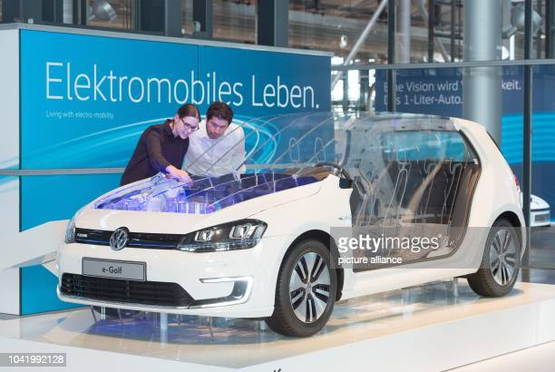People look at the model of a VW eGolf at the Transparent Factory of Volkswagen AG on occasion of a press tour in DresdenGermany 07 April 2016 The...