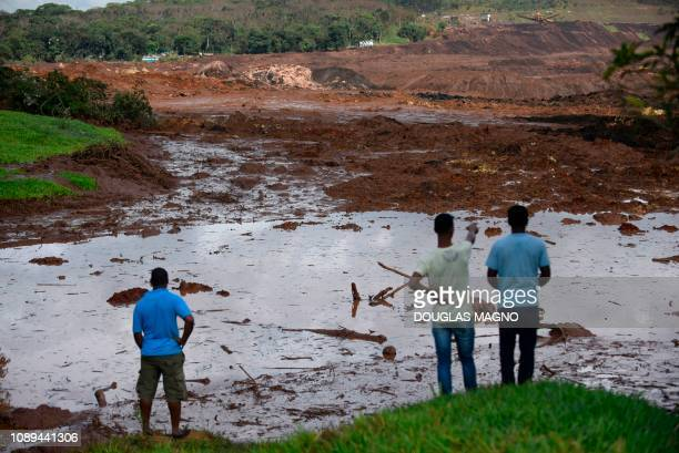 TOPSHOT People look at the mudhit area a day after the collapse of a dam at an ironore mine belonging to Brazil's giant mining company Vale near the...