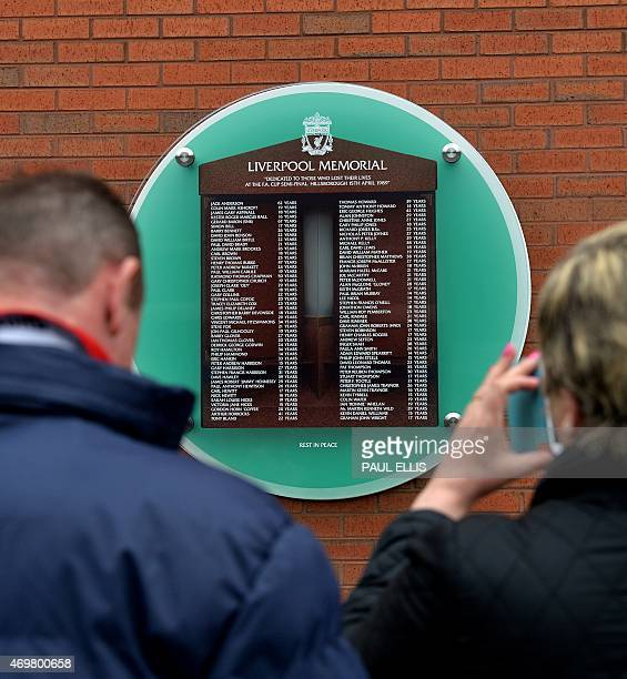 People look at the names on the temporary Hillsborough memorial ahead of a memorial service at Anfield in Liverpool north west Engand on April 15 on...