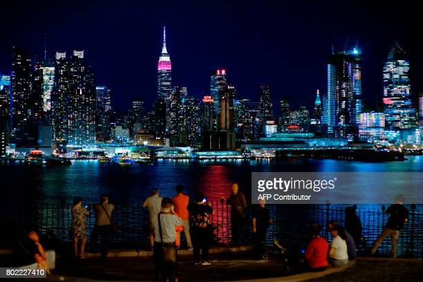People look at the New York skyline with the Empire State Building lit in burgundy and white in honor of Qatar Airways and its 10th Anniversary of...