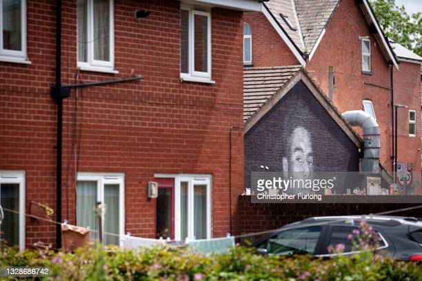 People look at the newly repaired mural of England footballer Marcus Rashford by the artist known as AKSE_P19, which is displayed on the wall of a...