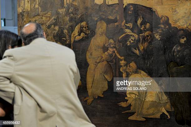 People look at the painting 'Adoration of the Magi' representing a nativity scene by Italian Renaissance master Leonardo da Vinci during its...