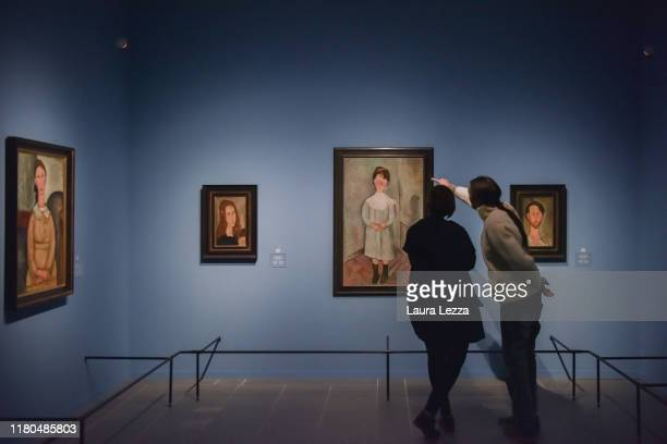 People look at the painting 'Fillet en blue' by Italian artist Amedeo Modigliani before the opening of the exhibition 'Modigliani and the...