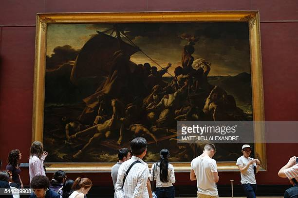 People look at the raft of the medusa painting by French Theodore Gericault on June 29 2016 at the Louvre Museum in Paris The painting depicts the...