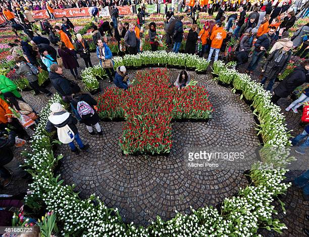 People look at the Red Cross logo made of tulips during Dutch National Tulip Day in front of the Royal Palace at Dam Square with the theme 'share joy...