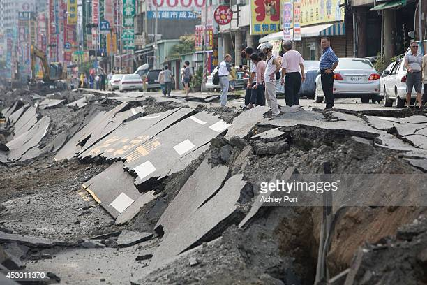 People look at the remains of a damaged road after several gas explosions took place in southern Kaohsiung on August 1, 2014 in Kaohsiung, Taiwan. A...