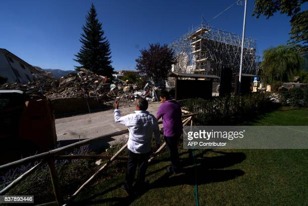 People look at the remains of Amatrice on August 23, 2017 a year after a deadly earthquake left nearly 300 people dead and destroyed the small town....