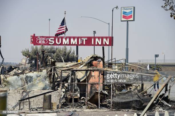 People look at the remains of the historic Summitt Inn after the Blue Cut Fire burnt the historic diner to the ground overnight at the top of the...