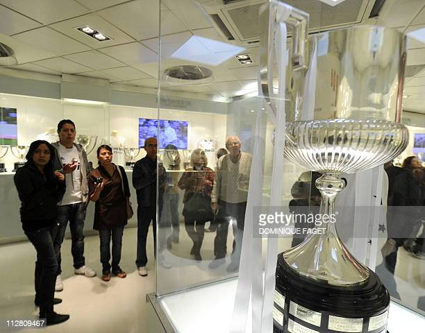 People look at the replica of the King's Cup on display at the museum of the Santiago Bernabeu stadium in Madrid on April 22 2011 Real Madrid has put...