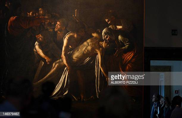 People look at the restored Caravaggio's painting 'Resurrection of Lazarus' at the Palazzo Braschi museum in Rome on June 15 2012 Painted by...