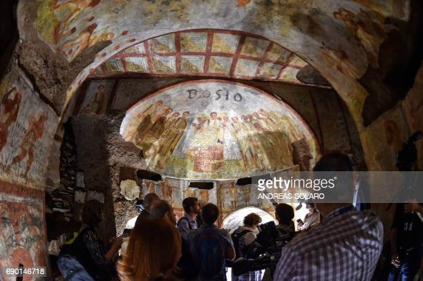 People look at the restored fresco dei Fornai cubicle during a visit after the restoration of the catacomb of Santa Domitilla in central Rome on May...