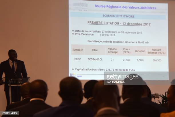 People look at the results of the first valuation of the panAfrican banking conglomerate Ecobank Cote D'Ivoire at the regional stock exchange Bourse...