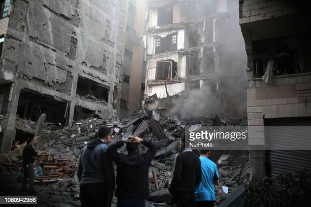 People look at the rubble of a building in Gaza City on November 13 after an Israeli air strike Renewed violence in Gaza threatened to thwart efforts...