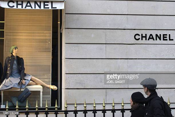 People look at the shop window of a Chanel store on December 26 2012 in Paris AFP PHOTO / JOEL SAGET