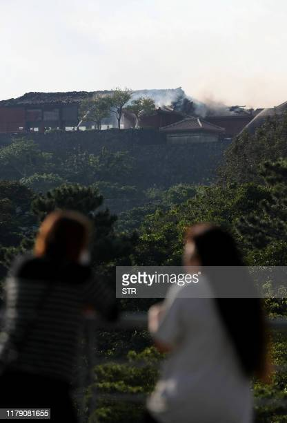 People look at the shuri Castle as smoke billows from the historic site in Naha Okinawa prefecture southern Japan on October 31 2019 A fire ripped...
