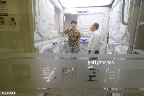 People look at the 'sleepsharing' capsules at a hotel in Zhongguancun on July 11 2017 in Beijing China Customers can rent the sleepsharing capsules...