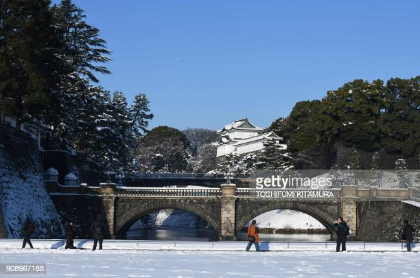 People look at the snow covered bridges of the Imperial Palace in Tokyo on January 23 2018 Tokyo woke up to snow across the city a day after heavy...