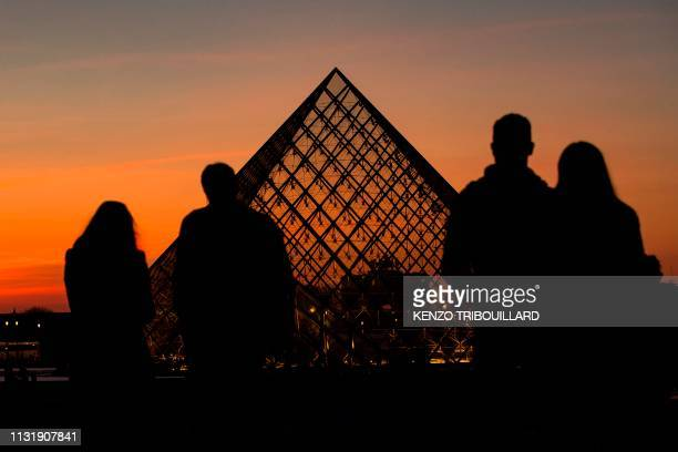 People look at the sunset behind the Louvre Pyramid in Paris, on March 21, 2019. - Chinese born US architect Ieoh Ming Pei's pyramid celebrates its...