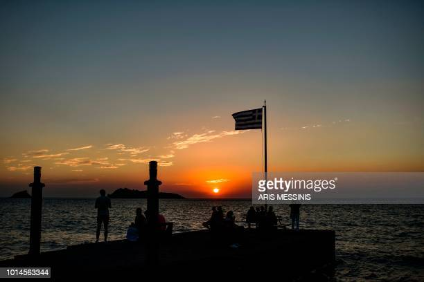 People look at the sunset from the beach of Petra in the northeastern island of Lesbos on August 4 2018