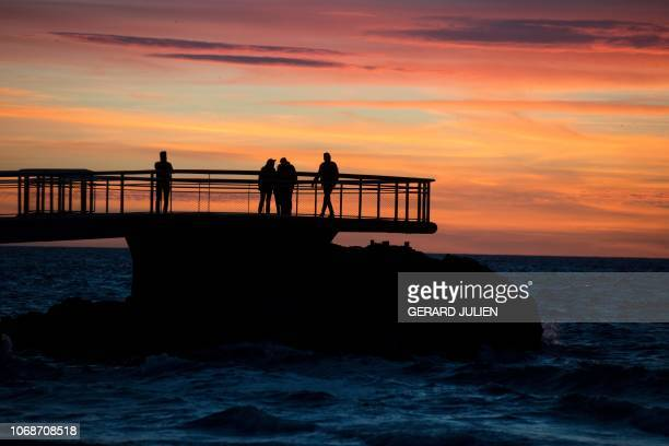 TOPSHOT People look at the sunset on the Mediterranean Sea since the Catalans beach with the Frioul's islands in the background on December 4 in...