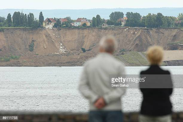 People look at the surviving half of a house standing over a landslide at the edge of Concordia Lake on July 20 2009 in Nachterstedt Germany A...