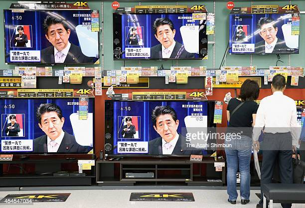 People look at the television screens showing Japanese Prime Minister Shinzo Abe during the press conference after naming the new cabinet members at...