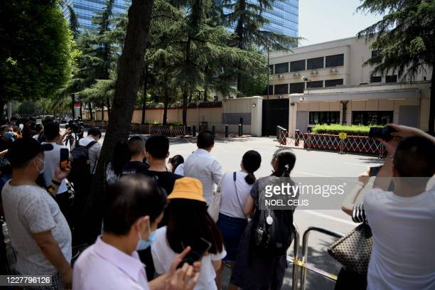 People look at the US Consulate in Chengdu, southwestern China's Sichuan province on July 27, 2020. - Chinese authorities took over the United States...