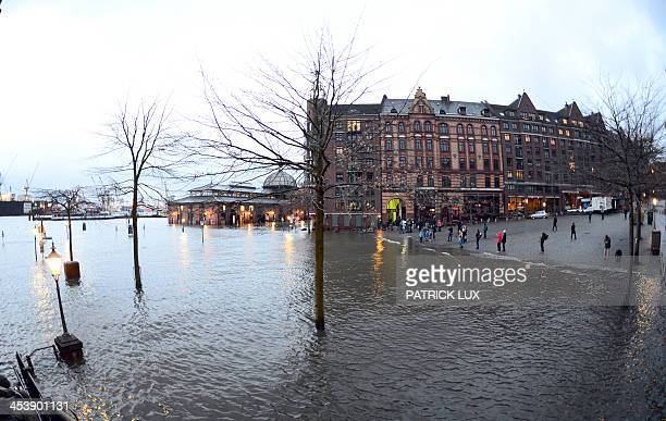 People look at the water level of the Elbe river near historic fish auction hall Fischmarkt remained flooded on December 06 2013 after the storm...