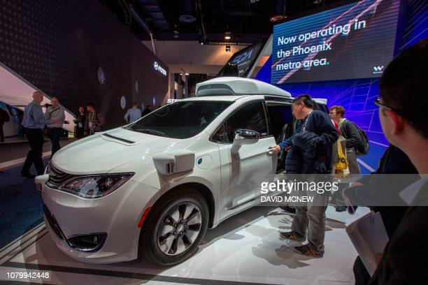 People look at the Waymo car, formerly the Google self-driving car project, during the Las Vegas Convention Center during CES 2019 in Las Vegas on...