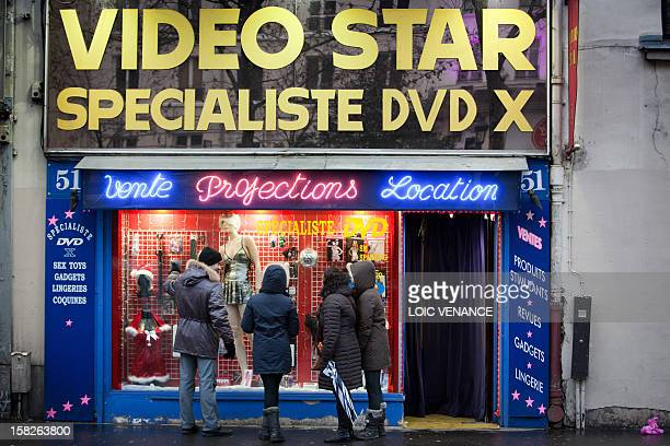 People look at the window shop of a sex shop on January 12 2011 in the Paris district of Pigalle AFP PHOTO LOIC VENANCE