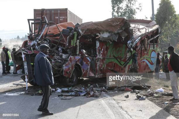 People look at the wreckage of a bus and a lorry that crashed in a headon collision killing thirty people at the accident scene near Nakuru Kenya on...