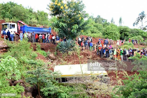 People look at the wreckage of a bus that had been transporting primary school pupils from Arusha to Karatu before plunging into a gorge killing at...
