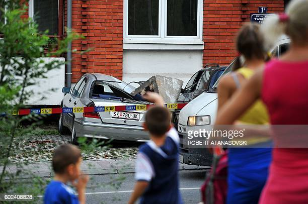 People look at the wreckage of a car after a chimney fell down near Skpoje, on September 11 following a moderate 5.3-magnitude earthquake, preceded...