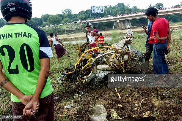 People look at the wreckage of a crashed military plane at a field in Magway on October 16 2018 A young girl and two pilots were killed on October 16...