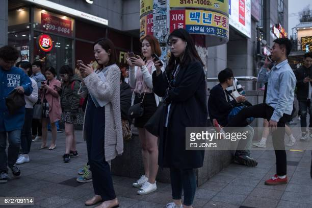 People look at their mobile phones as they stand on a street in the Hongdae district of Seoul on April 25 2017 / AFP PHOTO / Ed JONES