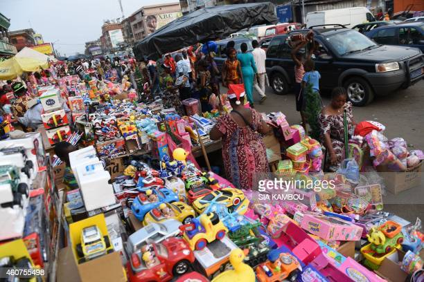 People look at toys on display at the Koumassi market in Abidjan on December 21 2014 ahead of Christmas holidays AFP PHOTO/ SIA KAMBOU / AFP PHOTO /...