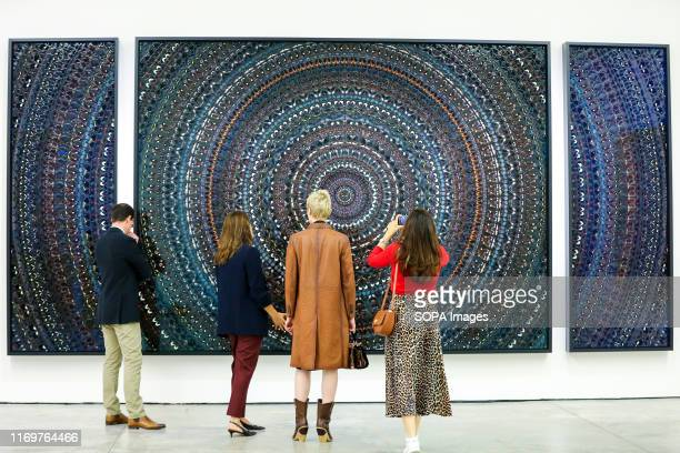 People look at Tranquility by artist Damien Hirst made up of butterfly wings and household gloss on canvas during the exhibition at the White Cube in...