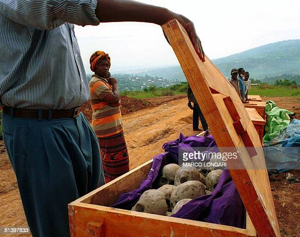 People look at unearth remains from a mass grave in Nyamirambo close to Kigali 05 April 2000 in preparation for dignified reburial as Rwanda marks...