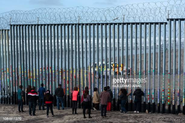 People look at US border patrol guards through the USMexico border fence in Tijuana in Baja California State Mexico on January 18 2019 A new caravan...