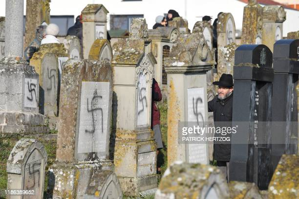 People look at vandalised tombs on December 4 2019 at the jewish Westhoffen cemetery near Strasbourg eastern France where 107 graves were found...