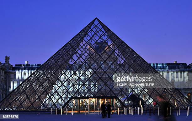 People look at Xenon for Paris a work by US conceptual artist Jenny Holzer projected on the Louvre museum's pyramid as well as the Louvre�s facade on...