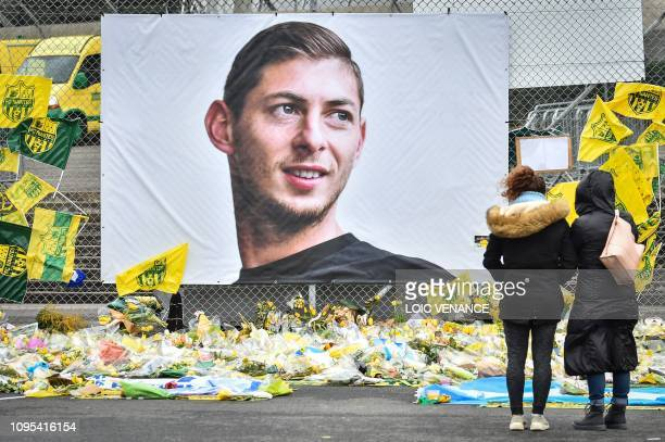 People look at yellow flowers displayed in front of the portrait of Argentinian forward Emiliano Sala at the Beauvoir stadium in Nantes, on February...