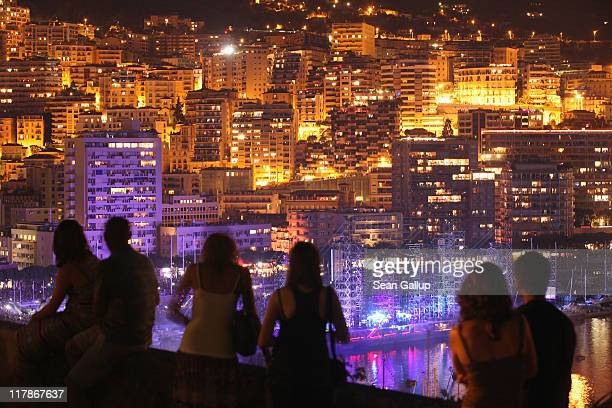People look down at a lightshow below during the Jean Michel Jarre concert celebrating the wedding of Prince Albert II of Monaco to Charlene...