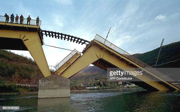 People look down from the destroyed railway bridge on the river Lim near Bistrica some 280 km southwest of Belgrade Thursday 15 April 1999 This main...